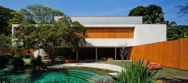 Massa branca, madeira e a textura do cobogó constituem a visualidade externa da casa.