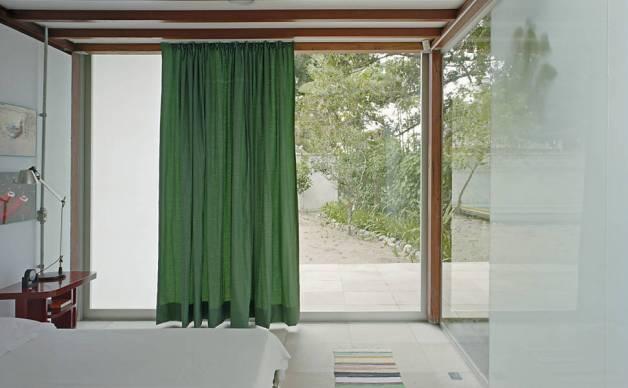No interior da casa o branco predomina, mas é quebrado pelas cortinas coloridas que também dão um colorido à fachada da casa.